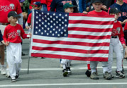 Young ball players proudly parade with American Flag