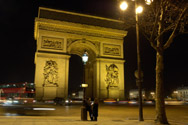 Bored tourists congregate around the Arc de Triomphe at night